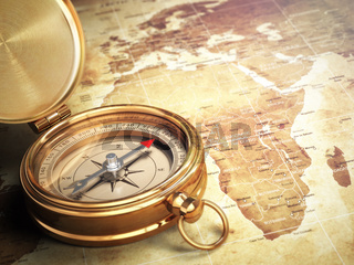 Vintage compass on the old world map. Travel concept.