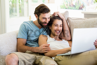 Couple sitting on sofa and using laptop