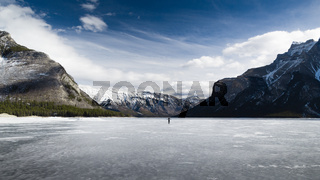 Alone woman on a frozen lake with Rocky Mountains in background