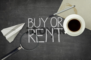 Buy or rent concept on black blackboard with empty paper sheet