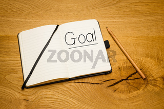 Notebook on office desk with goal text written with pencil.
