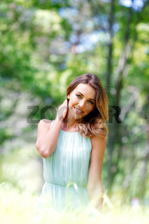 young woman in blue dress sitting on grass