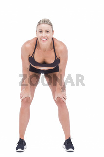 Female athlete with hands on knees