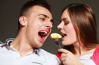 young couple eating banana fruit together