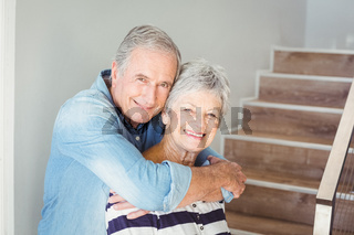 Portrait of cheerful senior couple embracing on staircase