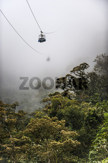 Tourists on cable chairlift above the jungle of Ecuador