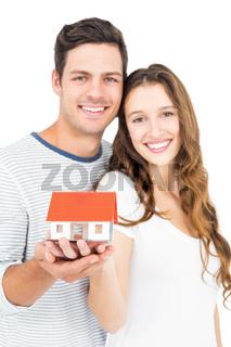 Happy couple holding miniature house