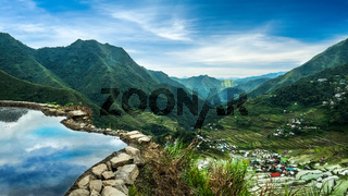 Amazing panorama view of rice terraces fields in Ifugao province mountains under cloudy blue sky. Banaue