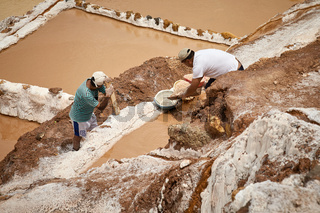 Workers at salina de Maras, the traditional inca salt field in Maras near Cuzco in Sacred Valley Peru