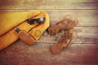Orange towel and beach items on wood