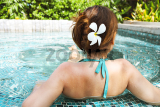Young beautiful woman relaxing in spa pool