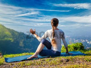 Woman practices yoga asana Marichyasana