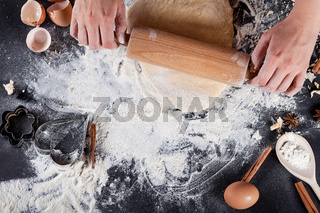 Baker is making  cookies with wooden rolling pin from the top