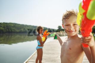 Junge mit Wasserpistole am See