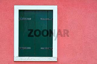 rosa Hausmauer mit grünem Fensterladen
