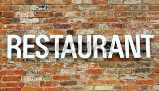 Old Restaurant sign on stone wall