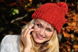 Junge Frau mit roter Mütze mit Smartphone