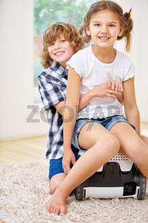 Glückliche Geschwister spielen mit Staubsauger