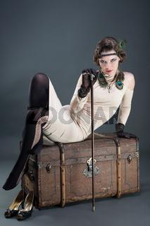 Schöne Frau im 20er Jahre Look auf Reisetruhe