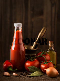 Dark still life with ketchup and ingredients on the rough wood