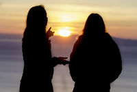 Silhouette of girls watching sunset
