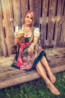 Hübsche Frau im Dirndl und Bierkrug in der Hand