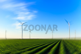Radial blurred image. Windmills at sunset at a field of crops in Eemshaven