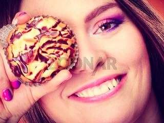 Funny woman holds cake in hand covering her eye