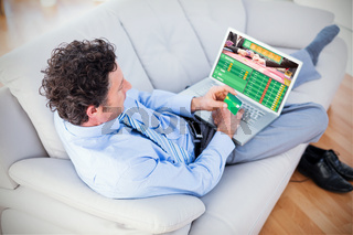 Composite image of businessman doing online shopping on couch