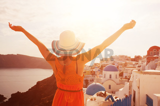 Happy woman in sun hat enjoying her holidays on Santorini