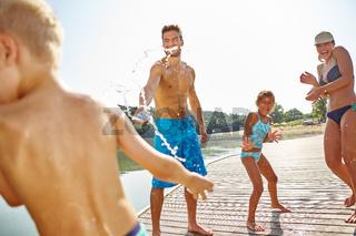 Glückliche Familie bespritzt sich mit Wasser
