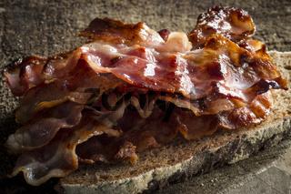 Eine Brotscheibe mit cross gebratenen Baconscheiben