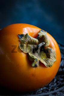 Eine Kahkifrucht als Stilleben vor dunklem Hintergrund