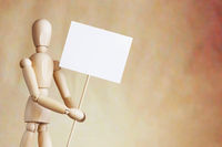 Wooden man holding blank white poster in its hands. Concept of declaration