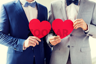 close up of male gay couple holding red hearts