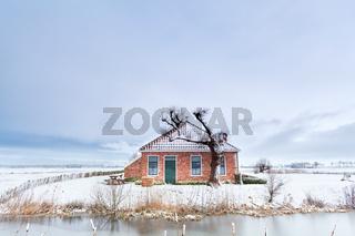 Dutch farmhouse by river in snow