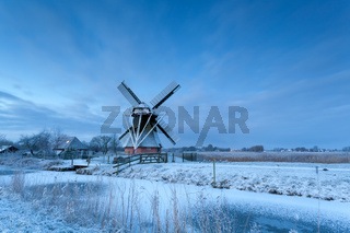 windmill in dusk during winter morning