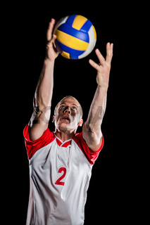 Sportsman catching a volleyball while playing