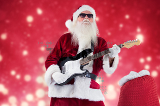 Composite image of santa claus plays guitar with sunglasses