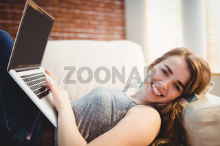 Pretty woman lying on the couch using her laptop