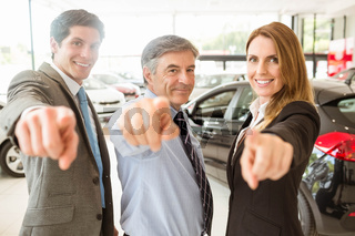 Group of smiling business team pointing together