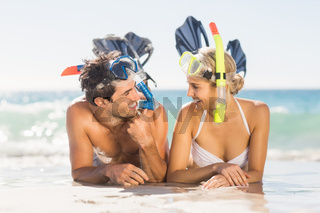 Young couple wearing diving mask lying on beach