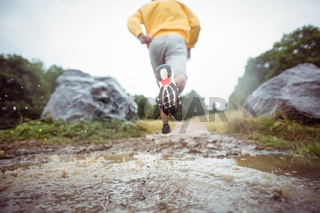 Man jogging through muddy puddles