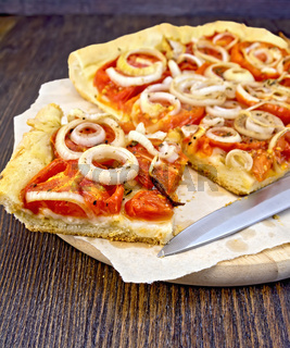 Pie with onions and tomatoes on parchment and board