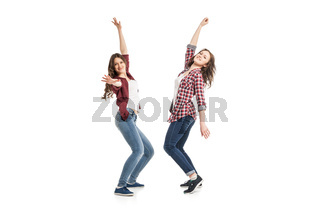 two young women dancing over white background