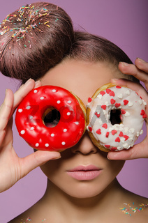 young woman with two donuts before eyes