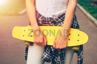 Girl in jeans and a plaid shirt holding a yellow plastic skateboard in hands