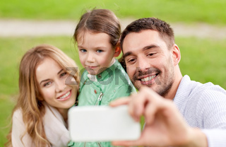 happy family taking selfie by smartphone outdoors