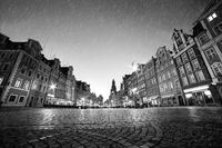 Cobblestone historic old town in rain at night. Wroclaw, Poland. Black and white
