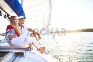 Young smiling couple on a sailing boat at summer
